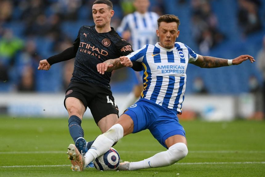 Brighton's Ben White (right) blocks a shot from Manchester City's Phil Foden during a Premier League match in May 2021.