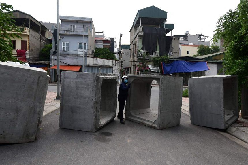 A woman squeezes through a make-shift barricade of concrete boulders in Hanoi on July 30, 2021.