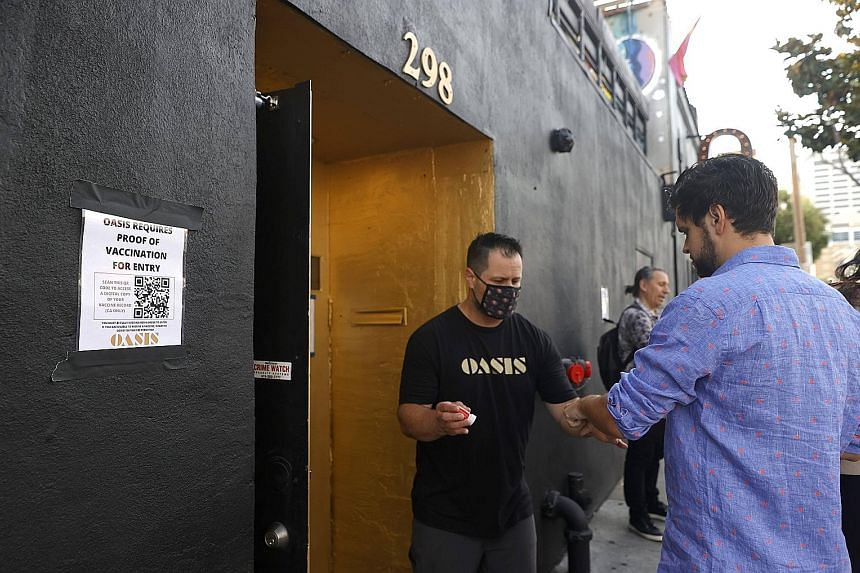 A doorman checking a customer's vaccination card before allowing him to enter a bar in San Francisco on Thursday. As at Monday, the four-week Covid-19 case count in the United States more than doubled from the previous four weeks. Cases and hospitali