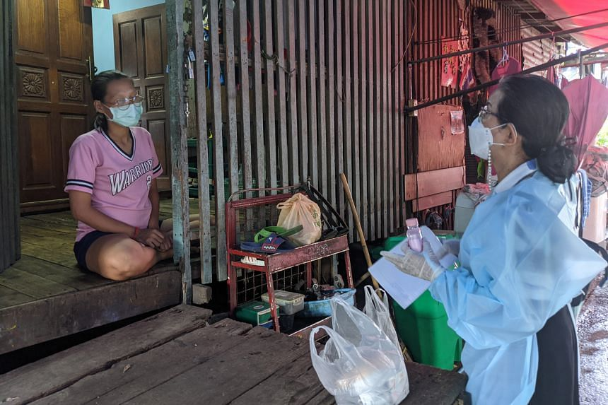 Ms Prateep Ungsongtham Hata (in PPE) checks in on a family in the Khlong Toey slum community that might have all been infected with Covid-19 on July 30, 2021.