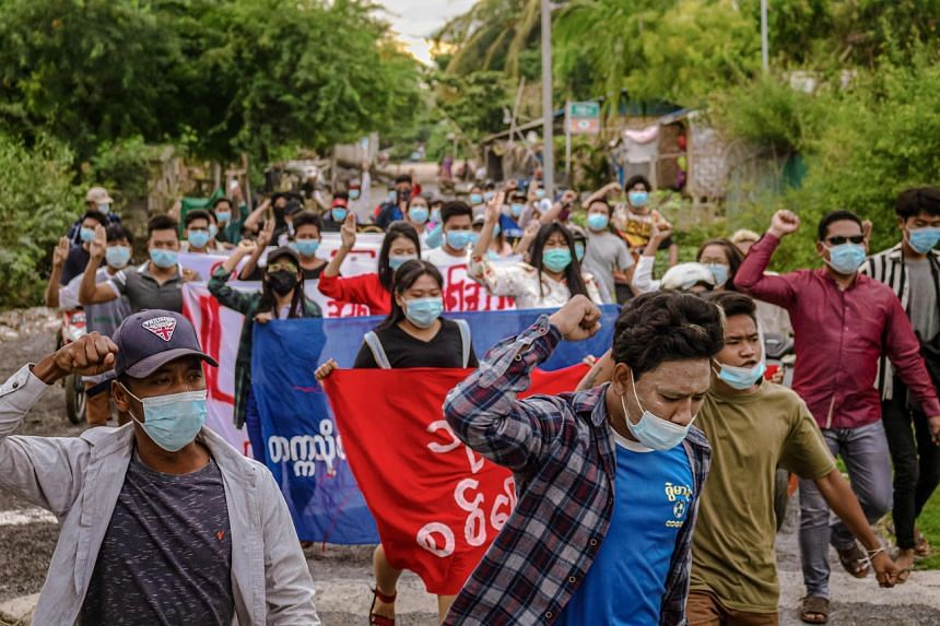 In a photo taken on June 11, 2021, protesters march during a demonstration against the military coup in Mandalay.