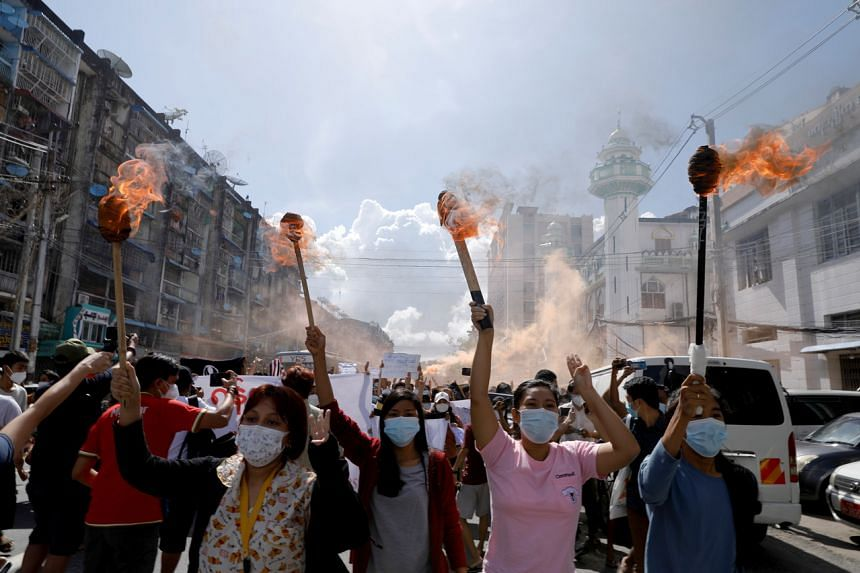 In a photo taken on July 14, 2021, a group of women hold torches as they protest against the military coup in Yangon, Myanmar.
