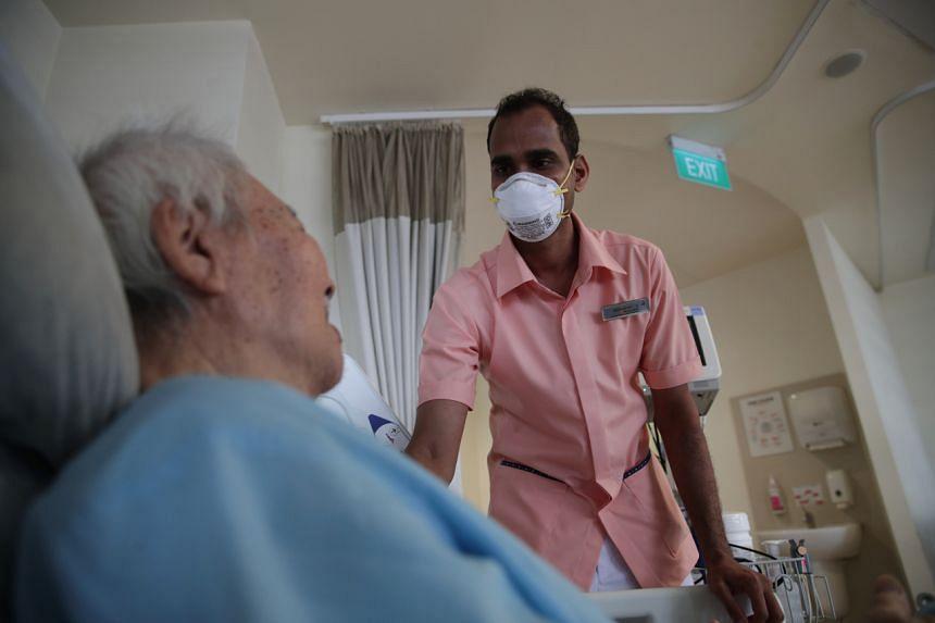 Healthcare assistant Ilandari Deva Nishantha with a patient at Jurong Community Hospital.