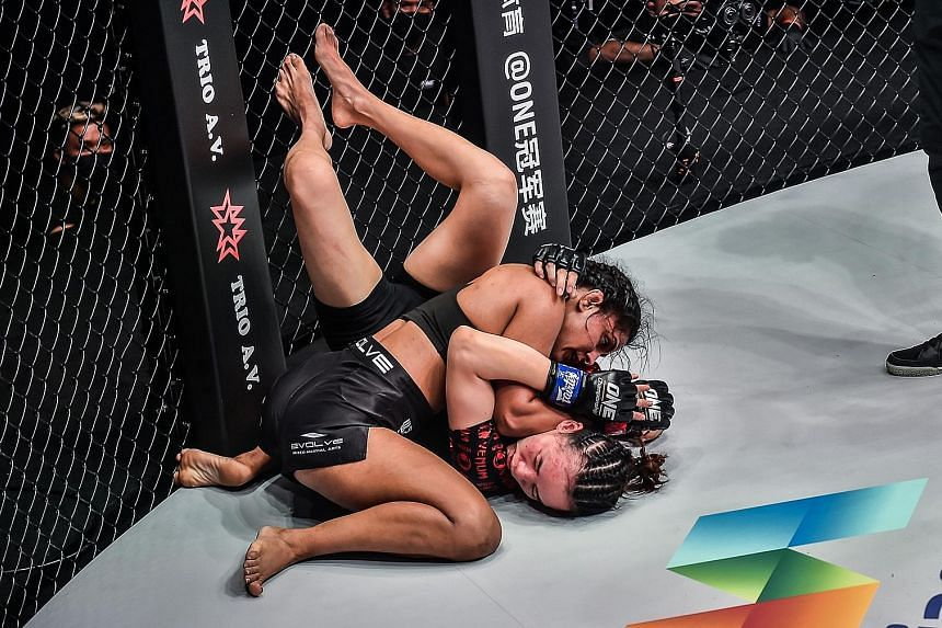"""Indian mixed martial arts fighter Ritu Phogat pinning down China's Lin Heqin in their atomweight bout at the One: Battleground event on Friday night. The """"Indian Tigress"""", who had lost her previous fight in May, got back to winning ways by claiming a"""