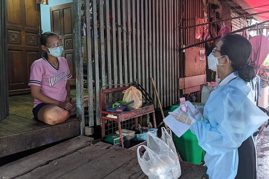 Ms Prateep Ungsongtham Hata (right), 69, who founded the Duang Prateep Foundation, reaching out to Ms Chuanpit Sopa, 27, who is five months pregnant, and her family in the Khlong Toey slum community in Bangkok. Ms Chuanpit, her husband and their daug