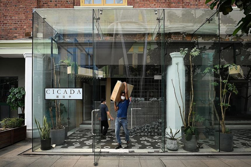 """Contractors clearing stuff from the almost empty Cicada restaurant in Clarke Quay yesterday. The restaurant, which opened early last year, had the Chinese name """"Yu Jian Li"""" - which means """"having met Li"""". It was apparently a gift from Ng Yu Zhi to one"""