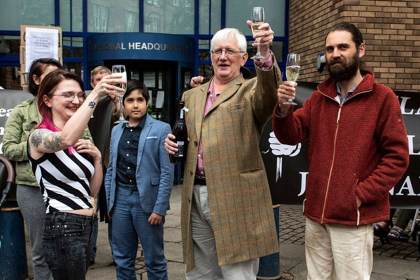 Britain's former ambassador Craig Murray (centre) with members of his family outside St Leonard's Police Station in Edinburgh on Aug 1, 2021.
