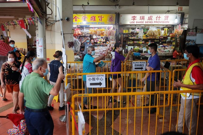 People checking in with TraceTogether at Yuhua Village Market and Food Centre on Aug 1, 2021.