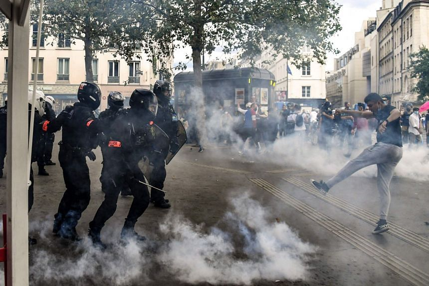 Demonstrators clash with police brigades in Paris at the end of a demonstration against the mandatory Covid-19 health pass, on July 31, 2021.