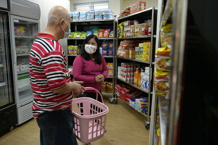 Ms Mariam Jaafar, an MP for Sembawang GRC, helping resident Toh Kok Jin to select groceries at Store@Woodlands.