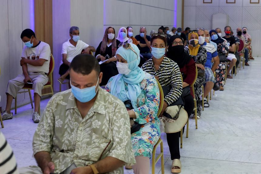People wearing masks wait to receive the COVID-19 vaccine at a vaccination centre in Tunis, Tunisia on Aug 1, 2021.