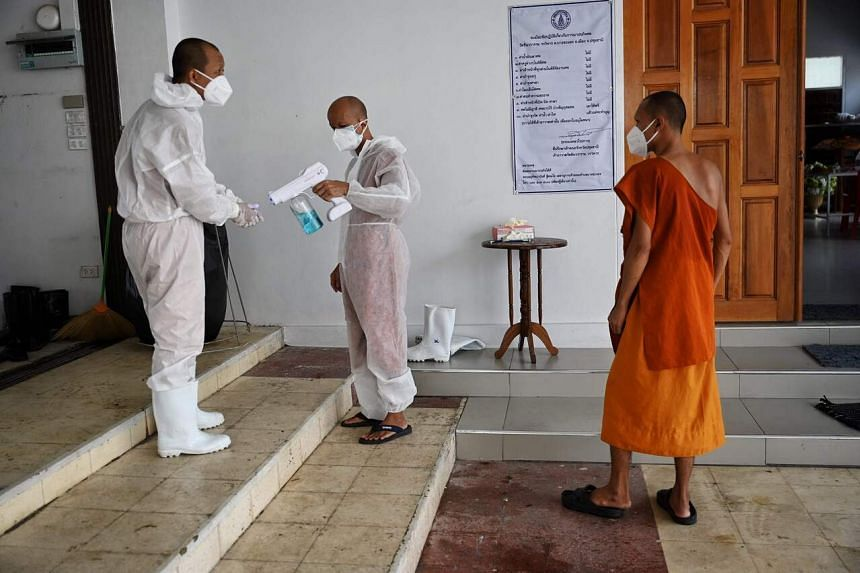 Buddhist monks disinfecting themselves after performing cremation duties for coronavirus victims in Bangkok on July 30, 2021.