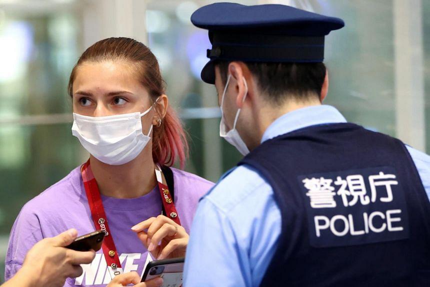 Krystsina Tsimanouskaya is escorted by police officers at Haneda International Airport in Tokyo, on Aug 1, 2021.