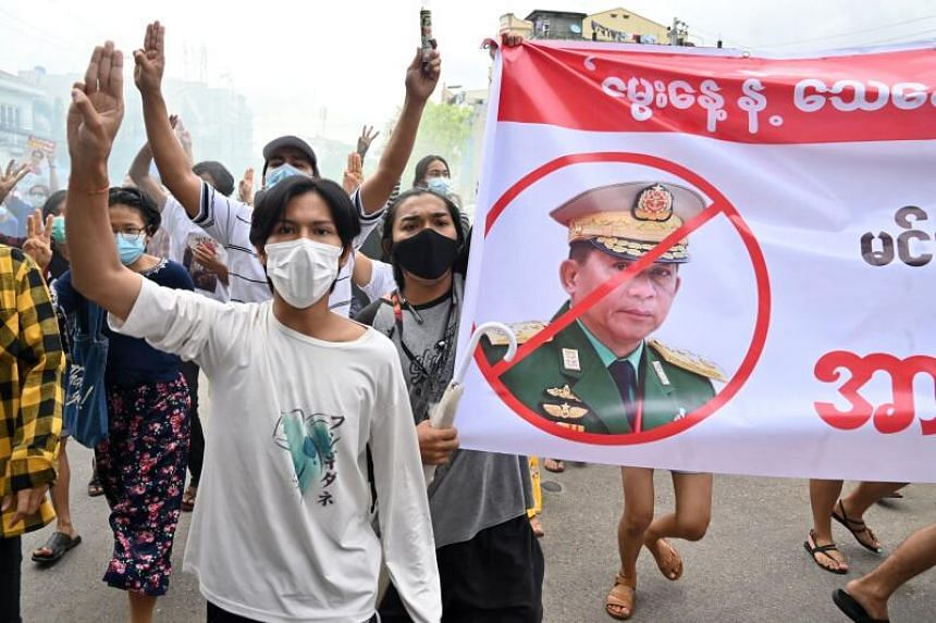 Protesters stand beside a banner protesting against Myanmar military chief Min Aung Hlaing during a demonstration in Yangon, on July 3, 2021.