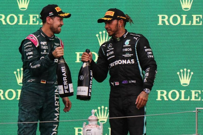 Sebastian Vettel and Lewis Hamilton celebrate with champagne on the podium after the Formula One Hungarian Grand Prix, on Aug 1, 2021.