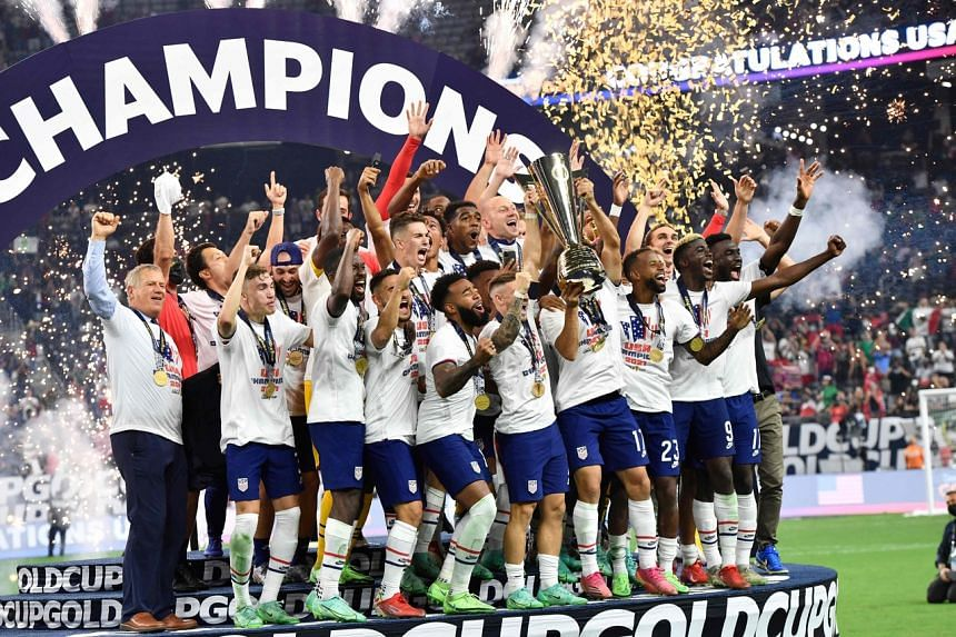 The US team celebrates on the podium after winning the final football match against Mexico at the Allegiant stadium in Las Vegas, on Aug 1, 2021.