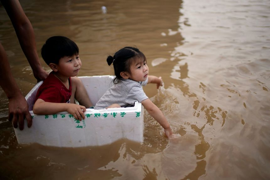 Children sit in a styrofoam container on a flooded road following heavy rainfall in Zhengzhou, Henan province, on July 22, 2021.