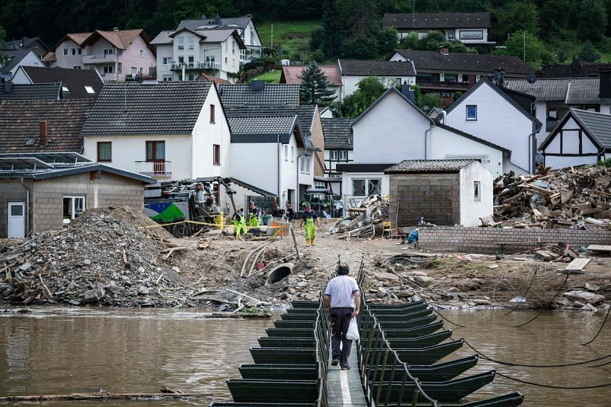 A man walks across a temporary bridge on Ahr river in the village of Rech in western Germany on July 30, 2021, weeks after heavy rain and floods caused major damage.