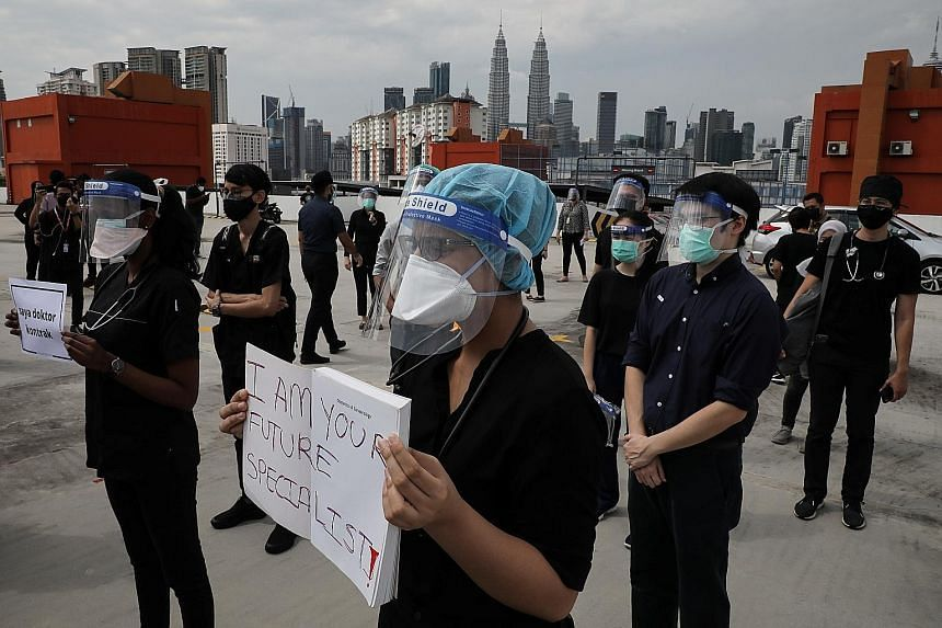 Government contract doctors dressed in black participating in a brief walkout at Kuala Lumpur Hospital on July 26, 2021.