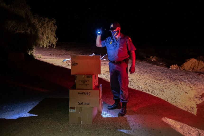 A police officer inspects boxes of illegally harvested plants during a sting operation near Steinkopf, South Africa, on Feb 2, 2021.