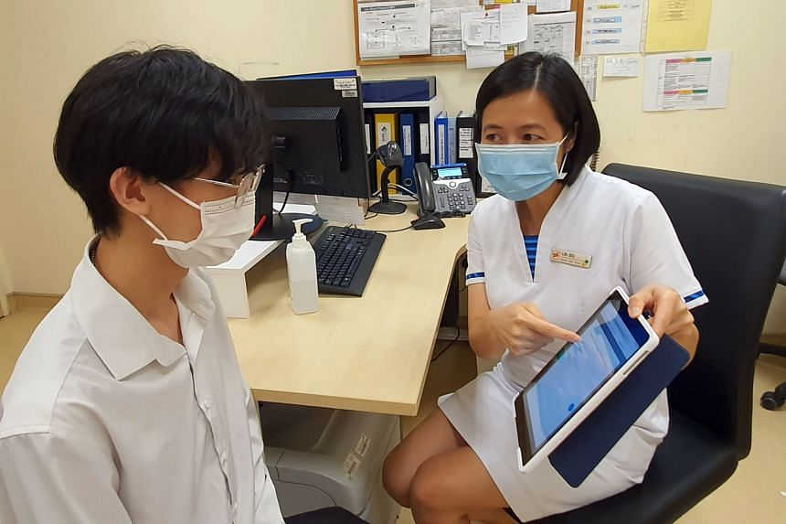 A polyclinic nurse using the smart triaging system on an iPad to help assess if a patient with chest pain has coronary heart disease.