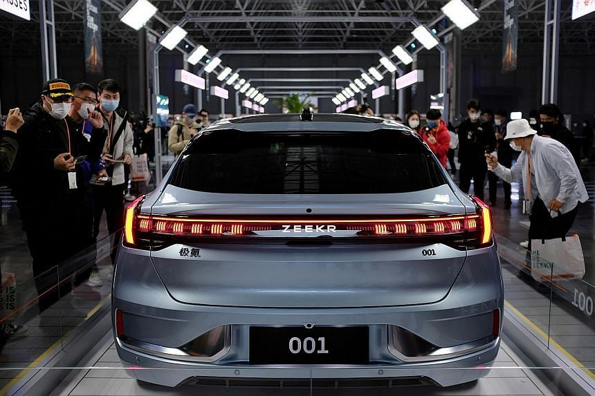 Visitors checking out the 001, a model from Geely's new premium electric vehicle (EV) brand Zeekr, at its factory in Ningbo, in China's Zhejiang province, in April.
