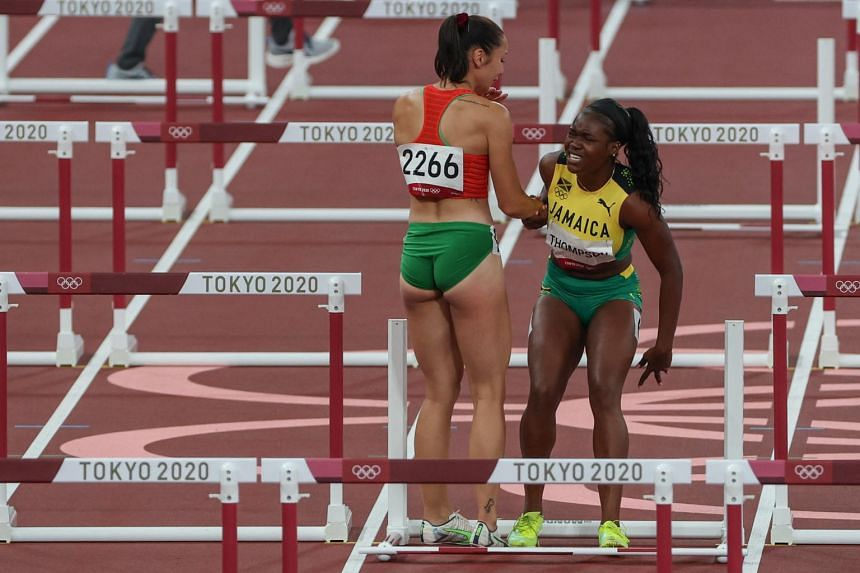 Luca Kozak (left) and Yanique Thompson react after falling in the women's 100m hurdles semi-finals at the Olympic Stadium in Tokyo on Aug 1, 2021.