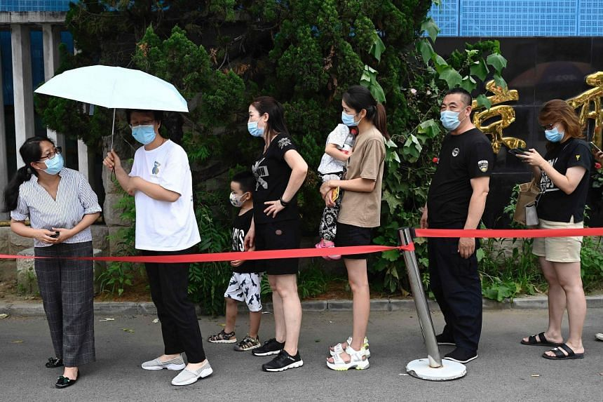 People queue up to be tested for the Covid-19 coronavirus at a hospital in Beijing on August 3, 2021.