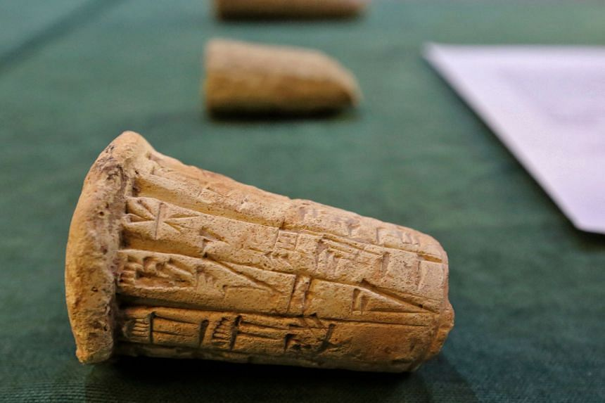 Mesopotamian clay cones bearing cuneiform inscriptions are displayed during a handover ceremony in Baghdad on Aug 3, 2021.