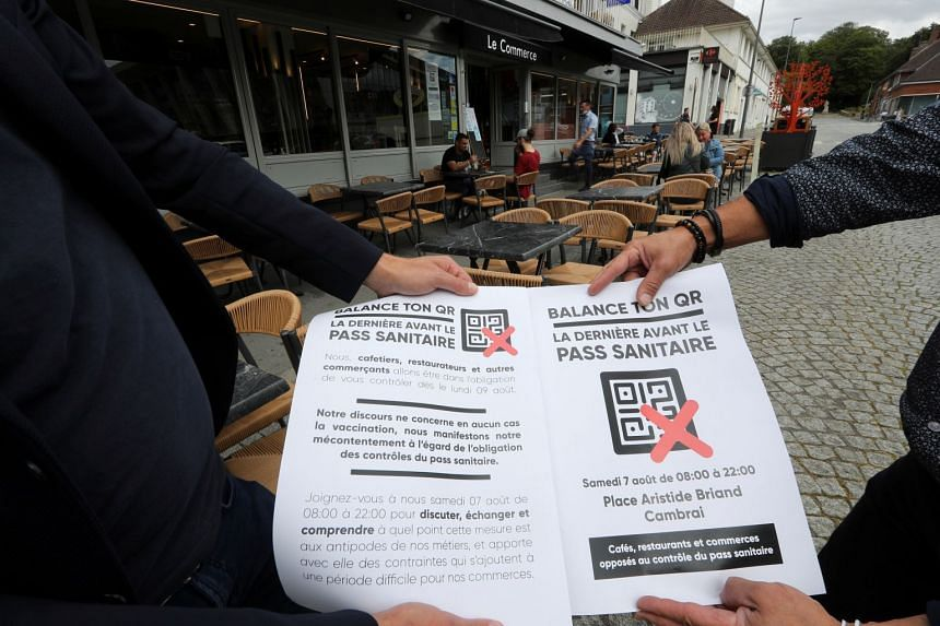 Two bar and restaurant owners hold a poster announcing a demonstration on Aug 7 against France's coronavirus safety restrictions, in Cambrai, France.