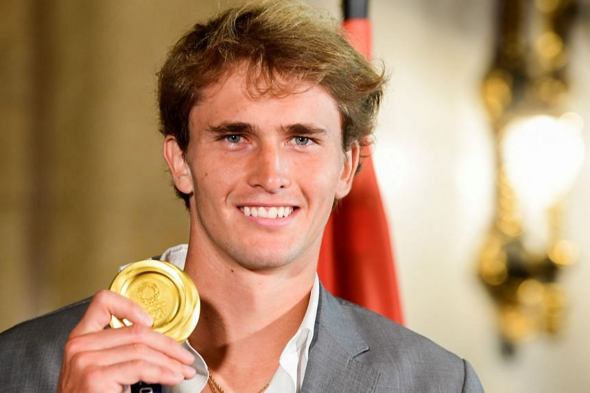 """Alexander Zverev shows off his gold medal during a """"Golden Book"""" signing at the town hall in Hamburg, Germany on Aug 3, 2021."""