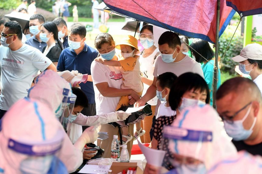 Residents line up for the mass Covid-19 test in a residential block in Wuhan on Aug 3, 2021.