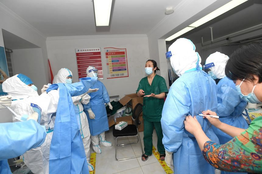 Medical workers prepare to take swab samples for the mass Covid-19 test in a residential block in Wuhan on Aug 3, 2021.