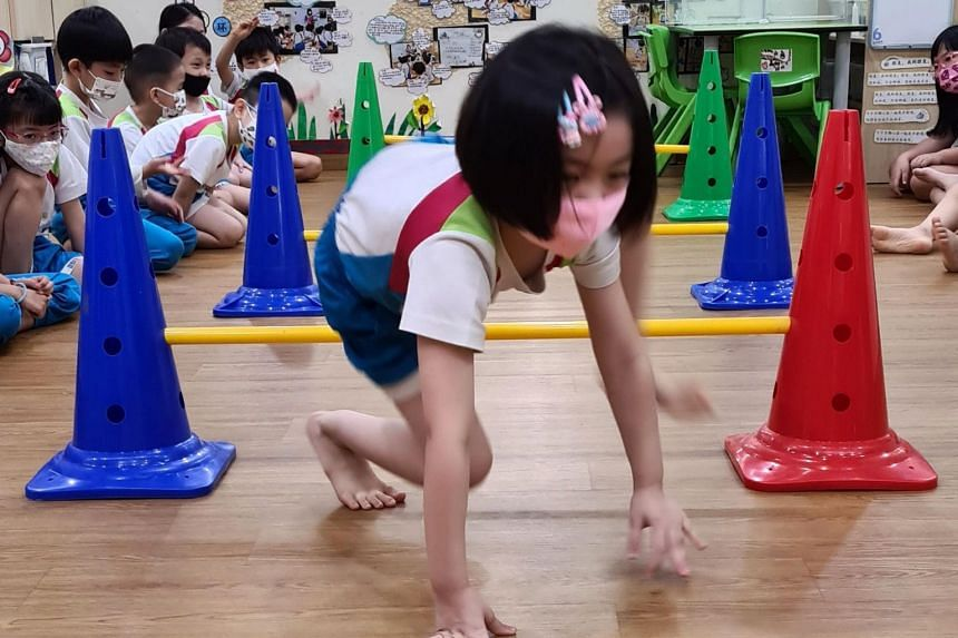 Pre-schoolers trying their hand at 'hurdling' as part of Kiddolympics.
