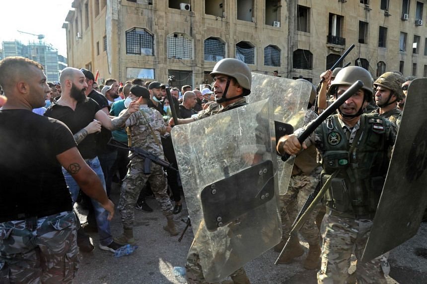 Security forces attempt to disperse protesters gathering outside the entrance to the port of Lebanon's capital on Aug 4, 2021.