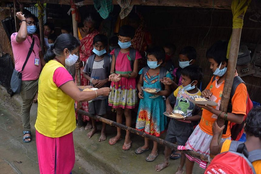 Children from a low-income neighbourhood receiving food distributed by a non-profit organisation, on the outskirts of Siliguri, India, on July 23, 2021.