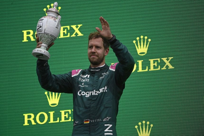 Aston Martin's Sebastian Vettel celebrates with his trophy on the podium before he was disqualified due to a technicality..