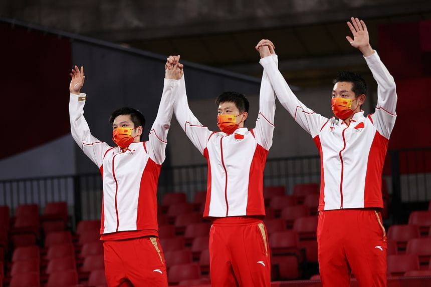 Gold medallists (from left) Xu Xin, Ma Long and Fan Zhendong of China celebrate on the podium.