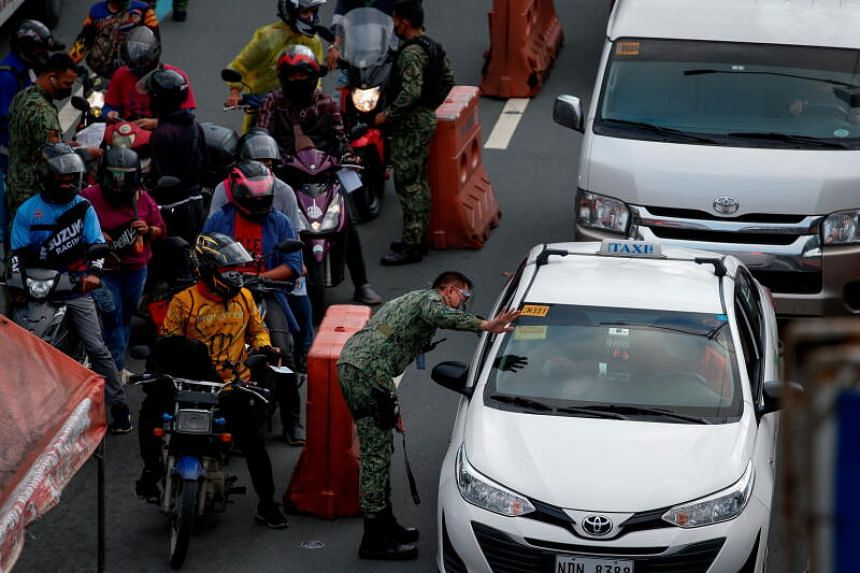 Police officers check identification of passing motorists at a checkpoint in the boundary of Quezon City and Manila in Metro Manila, Philippines, on Aug 6 2021.