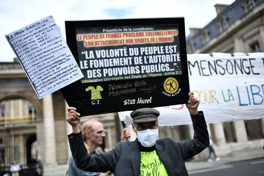 """A protester holds a sign reading """"The will of the people is the basis of the authority of the public powers,"""" during an anti-pass protest in Paris on Aug 5, 2021."""