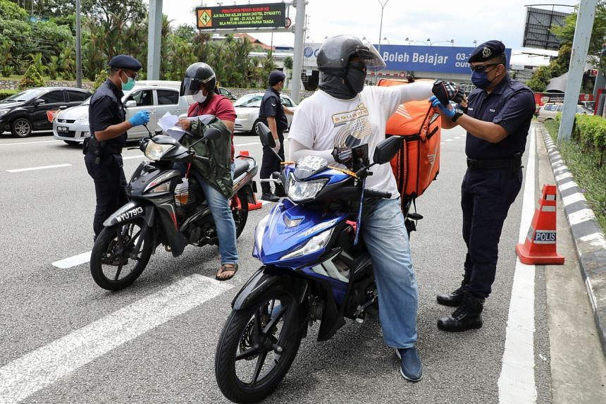 Police officers check riders at a road block during an enhanced lockdown in Kuala Lumpur on July 3, 2021.