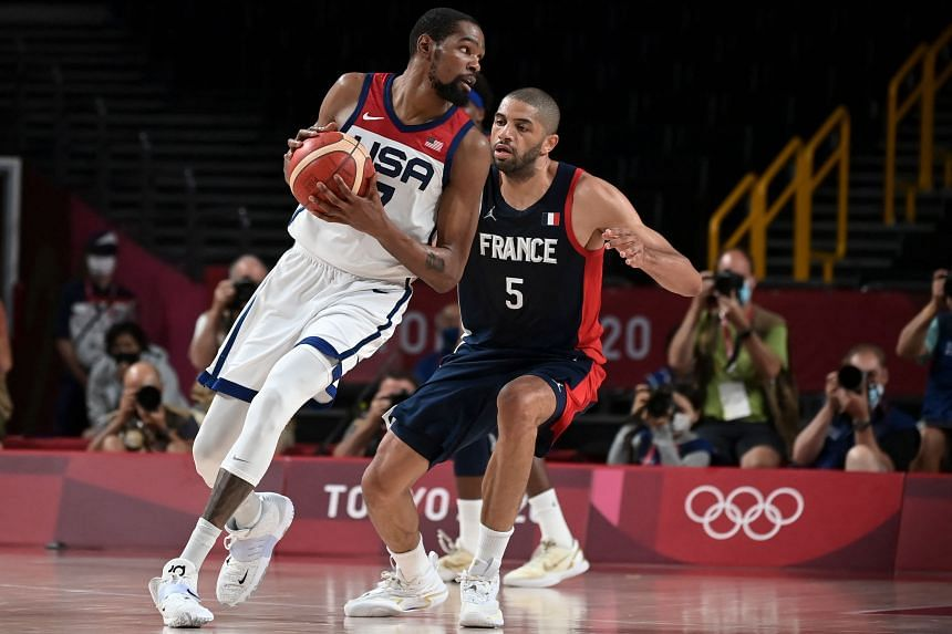 Kevin Wayne Durant (left) dribbles the ball in the men's final basketball match between France and USA at the Saitama Super Arena in Saitama, Japan, on Aug 7, 2021.