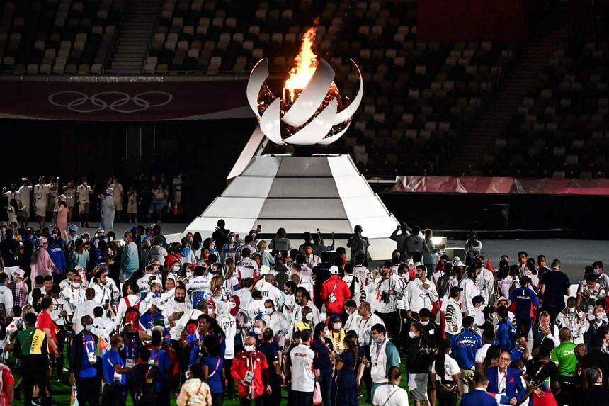 Athletes gather by the Olympic Cauldron during the closing ceremony in Tokyo, on Aug 8, 2021.