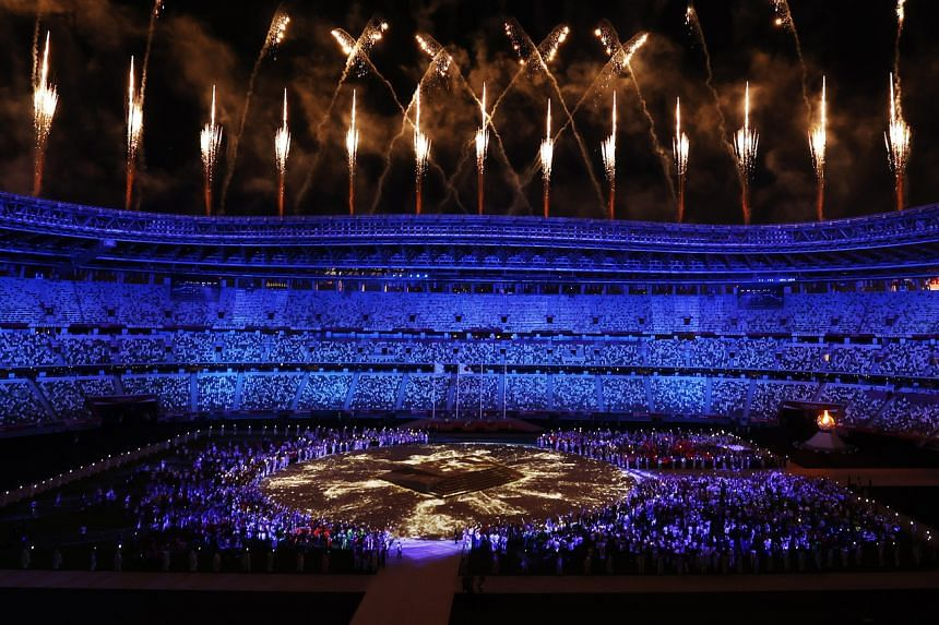 A volley of white-and-gold fireworks streaked above the Olympic Stadium.