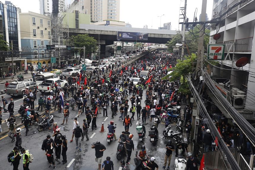 Protesters retreating after police fire tear gas during a march on the road to the Prime Minister's residence in Bangkok on Aug 7, 2021.