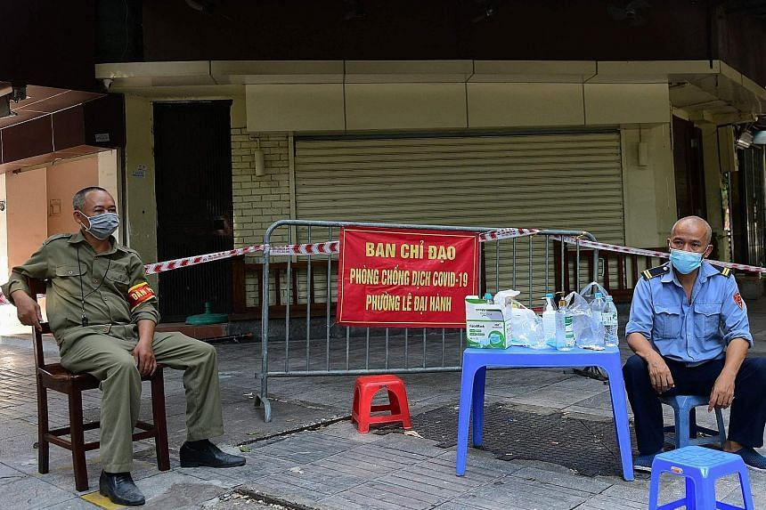 Guards outside a cafe closed due to curbs to halt the spread of Covid-19 in Hanoi on July 12, 2021.