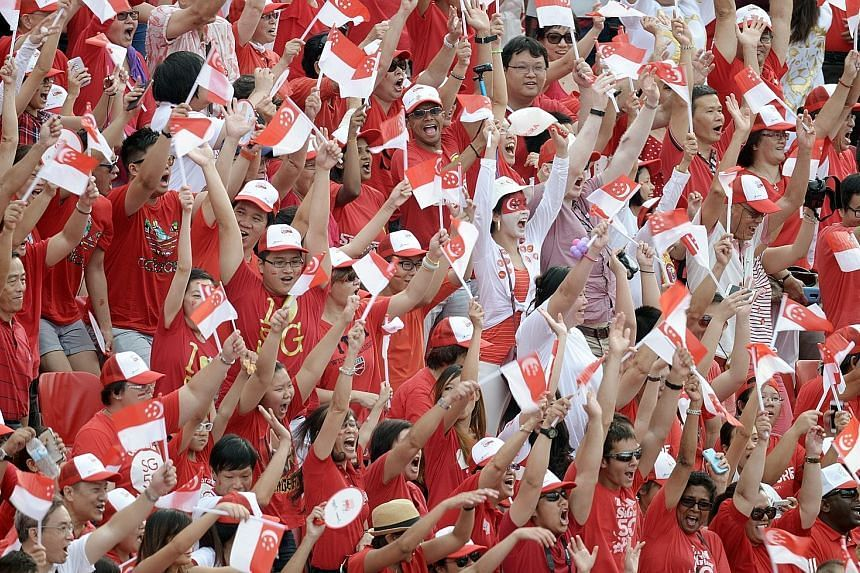 Spectators doing the Kallang Wave at the National Day Parade at the Padang in 2015.