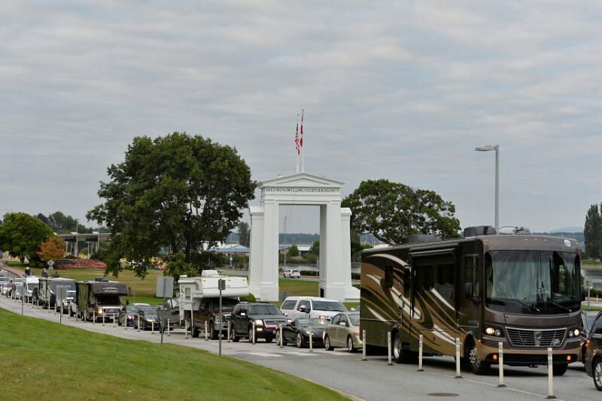 Travellers line up to enter Canada at the Peace Arch border crossing in Surrey, British Columbia, Canada on Aug 9, 2021.