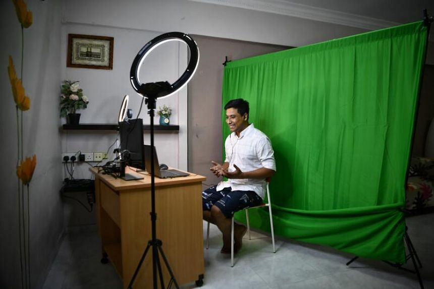 Nazmul Khan's live-streaming set-up consists of just a small table, two ring lights and a makeshift green screen.