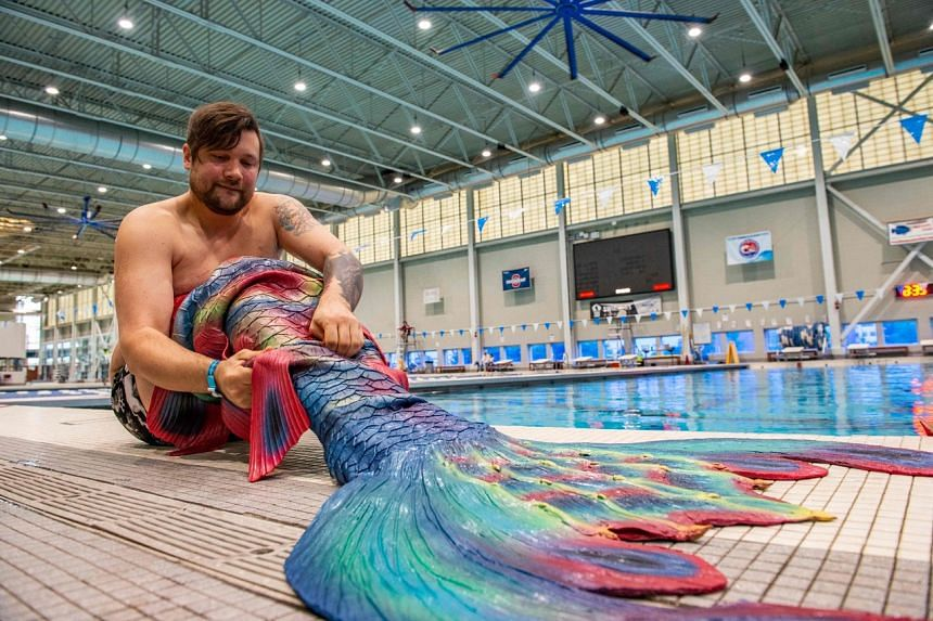 Christian Webber, 32, puts on his silicone tail, that cost him $5,500, during MerMagic Con on Aug 7, 2021.